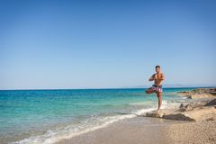 Adult man in yoga position, tree pose, on the waterfront, in Greece stock images