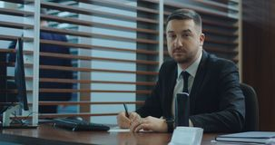 Manager writing in office. Adult manager in suit writing on paper and looking at camera in office stock footage