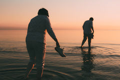 Adult married couple holds shoes in hand and walks on water. Royalty Free Stock Images