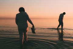 Adult married couple holds shoes in hand and walks on water. Royalty Free Stock Photography