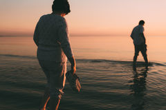 Adult married couple holds shoes in hand and walks on water. Stock Images