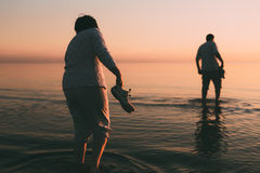 Adult married couple holds shoes in hand and walks on water. Stock Photo
