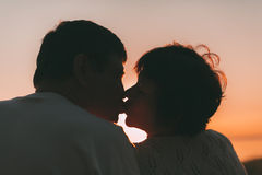 Adult married couple kiss against a sunset. Stock Image