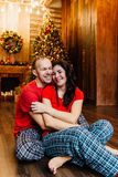 Adult married couple in red T-shirts and pajamas embraces sitting on the floor against the Christmas tree. Checkered pants stock photo