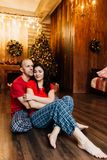 Adult married couple in red T-shirts and pajamas embraces sitting on the floor against the Christmas tree. Checkered pants stock photography