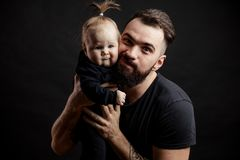Young athletic father with adorable baby on black background royalty free stock image