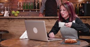 Adult mature businesswoman in her 40s having a video call conference. While drinking coffee in a vintage and styled coffee shop, restaurant or pub stock video footage