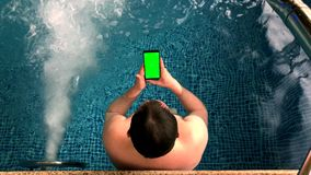 Adult men have rest in pool. Adult men in pool against Pool Water Jet hold water proof smartphone with green screen stock footage
