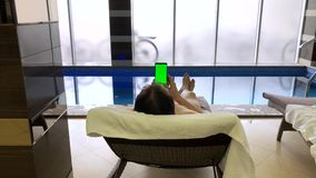 Adult men have rest in pool. Adult plus size men near by pool against Pool Water Jet hold water proof smartphone with green screen stock video