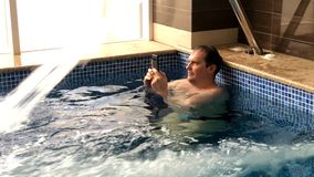 Adult men have rest in pool. Adult men in pool under Pool Water Jet hold water proof smartphone stock video