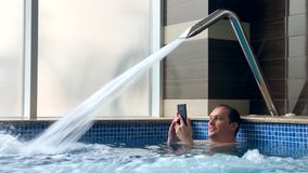 Adult men have rest in pool. Adult men in pool under Pool Water Jet hold water proof smartphone stock footage