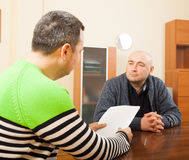 Adult men talking with documents. Two adult friends talking at home with documents stock image