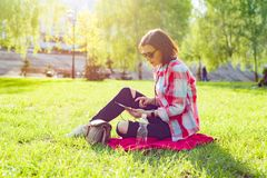 Adult middle-aged woman sits in city park stock photos