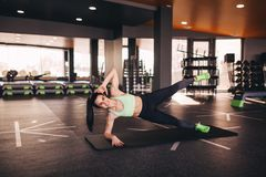 Cheerful woman doing abs exercise on mat stock image