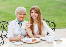 Adult mother and daughter drinking tea or coffee. Royalty Free Stock Image