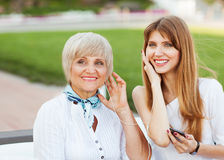 Adult mother and daughter listening to MP3 player Stock Photos