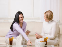 Adult mother and daughter playing cards. And enjoying ice tea and snacks at home Stock Image