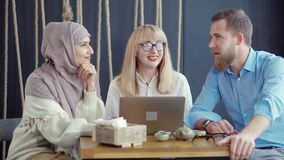 Adult multi ethnic friends are chatting in cafe in daytime. Two women and man are sitting in cafe in daytime and talking cheerfully. Multiethnic colleagues are stock video footage