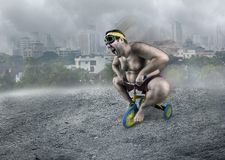 Adult naked man cycling on child's bicycle. Adult naked man cycling in the foggy street on child's bicycle Royalty Free Stock Photos