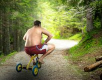 Adult naked man cycling on child's bicycle. Adult naked man cycling in the forest on child's bicycle Stock Images