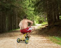 Adult naked man cycling on child's bicycle. Adult strange man cycling in the forest on child's bicycle Stock Image