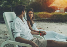 Adult newlyweds sitting on chaise longue on a beach. Caucasian beautiful women and her husband sitting on white beach chairs, holding hands of each other and stock images