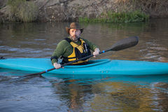 Adult paddler in blue kayak Stock Images