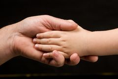 Adult palm holding child's hand Royalty Free Stock Image