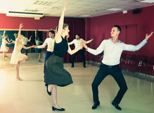 Adult people dancing lindy hop in pairs. In dance hall Stock Photos