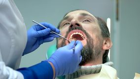 Adult person at the dentist. Doctor is checking teeth. Free dental diagnostics stock footage