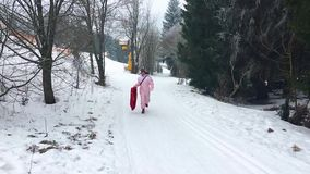 Adult person running up a snow hill with a sleigh, popular toys for adults and kids, Winter sports and fun stock footage