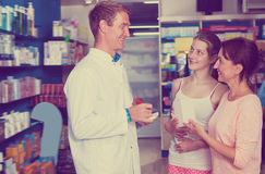 Adult pharmacist helping customers Royalty Free Stock Photo