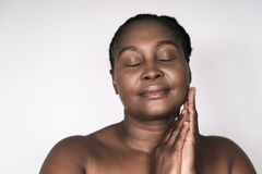 Content mature African woman standing with her eyes closed stock photography