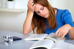 Adult pretty student girl reading a book. Portrait of a adult pretty student girl reading a book at study room Royalty Free Stock Images