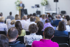 Adult Professionals Listening to the Lecturer Speaking on Stage During a Conference Royalty Free Stock Image