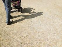 Adult Pushing Stroller Royalty Free Stock Image