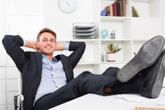 Adult relaxed man sitting with feet up on desk Stock Image