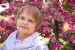 Adult Russian woman under pink flowers in park Royalty Free Stock Images