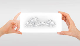 Adult's hand and child's hand holding white paper with abstract forest image. White background Stock Photos