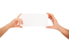 Adult's hand and child's hand holding white paper, cardboard.  Stock Images