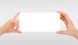 Adult's hand and child's hand holding white paper, cardboard. Stock Photography
