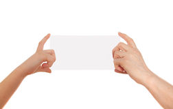 Adult's hand and child's hand holding white paper, cardboard. White background with space for text Royalty Free Stock Image