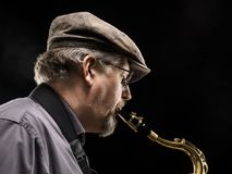 Adult sax player with his instrument. In studio Stock Photography
