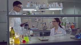 Adult scientists at work talking and smiling. Two doctors in medical or biological lab discussing medical tests . Woman and man in microbiological laboratory stock video footage