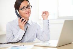 Adult secretary talking on the phone Royalty Free Stock Photos