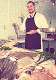 Adult seller in black apron showing fish Royalty Free Stock Photos