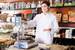 Adult seller weighing festive chocolate cake. In confectionery Royalty Free Stock Photos