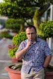 Adult senior man vaping electronic cigarette outdoor Stock Photo