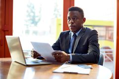 Serious black businessman with papers. Adult serious black man in suit sitting at table with laptop and papers looking unemotionally away stock photos