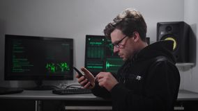 Adult serious man, looking like Hacker, with a small stubble on the face, points on the eyes, wearing a black hoodie stock video